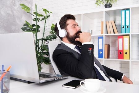 Mental health. Calming exercises. Calming activities. Crisis management. Inspiration concept. Boss at his workplace. Manager with headphones listening peaceful melody. Relaxing and calming down Imagens