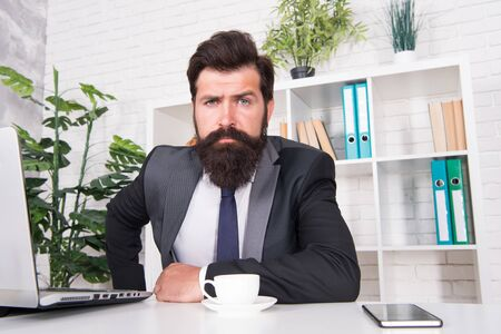 So confident. Brutal look of hipster man. Hipster sit at work desk. Businessman wear hipster beard. Bearded man in formal style. Barbershop or barbers. Fashion and style. Identical hipster
