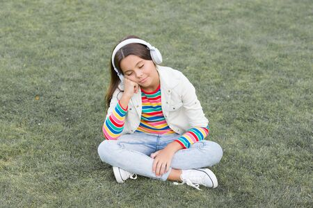 doze off. enjoy spring nature outdoor. child study audio book. new technology. Child listen music on green grass. Healthy lifestyle and relax. Yoga girl. small kid in headphones. summer playlist