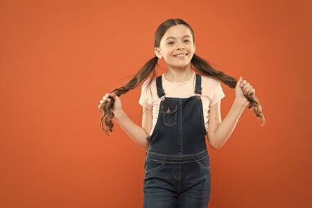 Wellbeing and health. Childhood concept. Fashion girl. Girl adorable kid stand over orange background. What is key to childhood happiness. Happy childhood. Grow mentally and physically healthy child