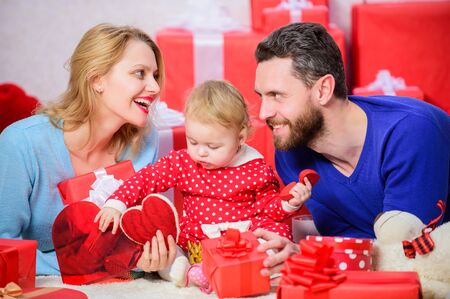 Shopping. Boxing day. Happy family with present box. Love and trust in family. Bearded man and woman with little girl. Valentines day. Red boxes. father, mother and doughter child. I am in love