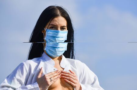 woman nurse in respirator mask cover bare breast. breast cancer concept. coronavirus pandemic outbreak. platic surgery. put silicone implant in boobs. medical care. sexy doctor