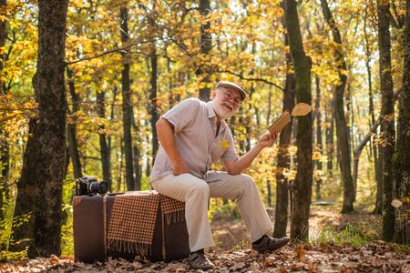 Hobby and leisure. Grandfather with vintage suitcase in nature. United with nature. Weekend in nature. Vacation and relax. Retirement concept. Elderly people. Mature man with white beard in forest