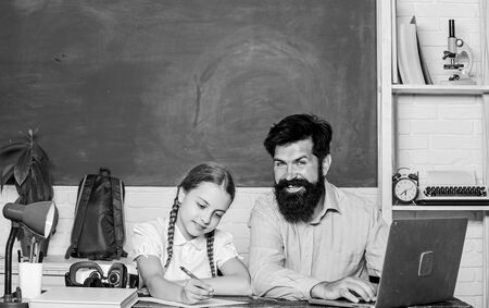 Private lesson. School teacher and schoolgirl with laptop. Study modern technologies. Homeschooling with father. Find buddy to help you study. Man bearded pedagogue teaching informatics. Study online