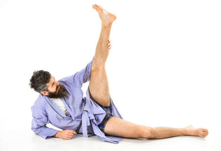 Morning exercise concept. Hipster with beard wears bathrobe