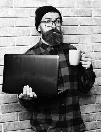 Bearded brutal caucasian hipster holding laptop with cup Stock fotó