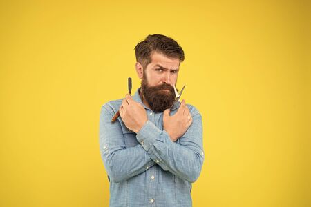 Shaving with a real blade sounds cool. Bearded man prepare shaving tools yellow background. Hipster hold shaving razor and scissors. Professional shaving from master barber. Shave barbershop