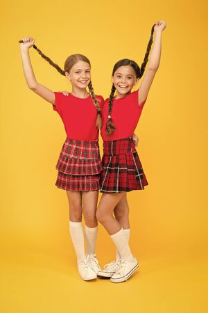 True friends. Happy small girls wearing same outfits. Friends enjoying friendship. Cheerful friends. Happy together. School girls having fun together. Cute little girls smiling yellow background