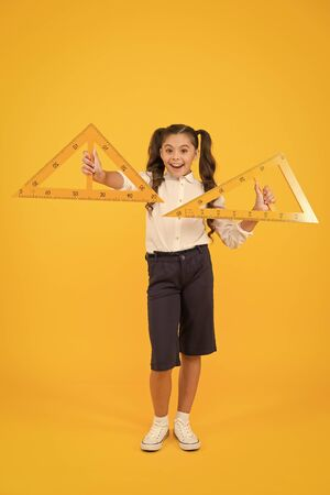 Learning geometry in school. School kid holding measuring instruments on yellow background. Cute little pupil preparing triangles for school lesson. Small girl is back to school