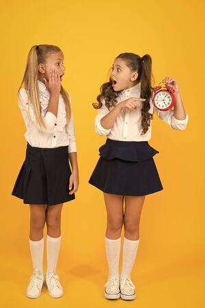 We are late for class. Stressed small children pointing at clock that running late on yellow background. Little girls making late school application. Its never too late to study