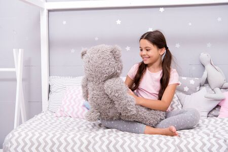 Play games. Favorite toy. Girl child hug teddy bear in her bedroom. Pleasant time in cozy bedroom. Girl kid long hair cute pajamas relax and play plush teddy bear toy. Imaginary interaction