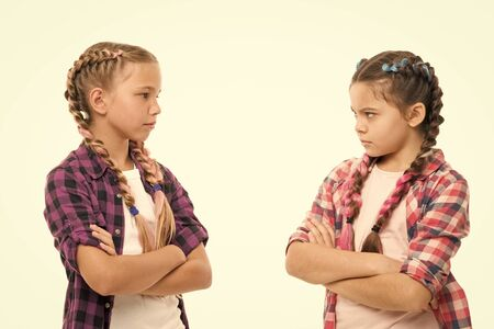 Kids sisters looks strictly. Girls folded arms on chest looks serious white background. Stubborn temper. Stubborn concept. Stubborn kids. Disagreement and stubbornness. Girls offended friends Foto de archivo