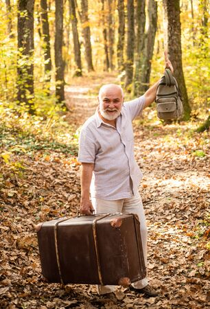 Retirement concept. Elderly people. Mature man with white beard in forest. Hobby and leisure. Grandfather with vintage suitcase in nature. United with nature. Weekend in nature. Vacation and relax