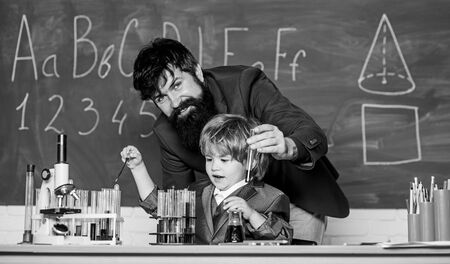 using microscope in lab. father and son at school. student doing science experiments with microscope in lab. Back to school. teacher man with little boy. school lab equipment. Preparing to exams