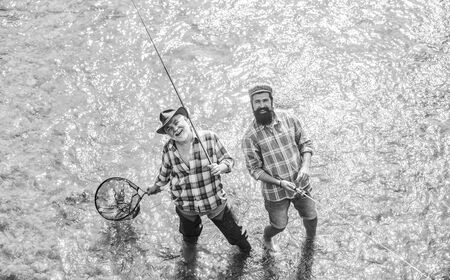 Collaboration. two happy fisherman with fishing rod and net. father and son fishing. Poaching. Camping on the shore of lake. Big game fishing. friendship. concept of rural getaway. hobby. wild nature Stock Photo