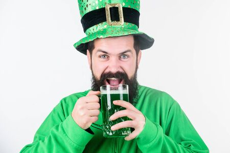 Irish culture. Man bearded hipster funny hat drink pint beer. Colored green beer. Green beer part of celebration. Irish pub. Alcohol consumption integral part saint patricks day. Cheers concept 免版税图像