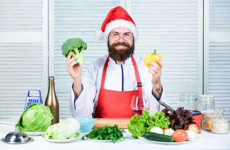 Man bearded chef wear santa claus hat cooking. How to enjoy holiday meals. Christmas diet. Enjoy healthy christmas dinner. Healthy christmas holiday recipes. How make your christmas dinner healthier