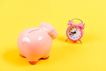 It is time to pay. Credit debt. Piggy bank pink pig and little alarm clock. Financial crisis. Economics and finance. Banking account. Bankruptcy and debt. Pay for debt. Bank collector service. Stockfoto