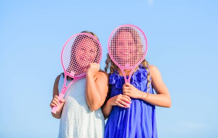Girls team. Small girls with pink tennis racket. Summer leisure. Sport game. Active life. Children play tennis blue sky background. Sporty kids. Playful cheerful kids. Happy childhood. Positive.