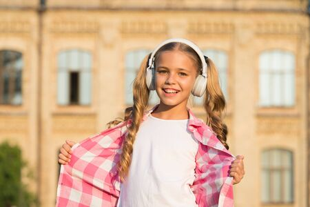 Wherever i go. Back to school. Small girl in headphones. Listening audio book. Free ebook. Girl in headphones listening music. Learning concept. Home schooling online education. Smiling schoolgirl