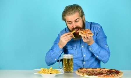 Still hungry. Beer and food. Dinner at pub. Hungry man going to eat pizza french fries and drink beer. Pizzeria restaurant. Cheerful man bearded hipster eat pizza. Pizza party concept. Good appetite