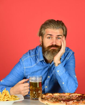 american fast food. bearded man with beer and pizza. italian food. French fries. guy in bar drinking beer glass and eating pizza. Cheers. watching football on TV Stock fotó