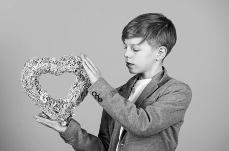 Beautiful heart. Small boy hold wicker heart. Little child with heart shaped decor. Decoration for Valentines day. Holiday of love and romance. My heart is wherever you are Foto de archivo