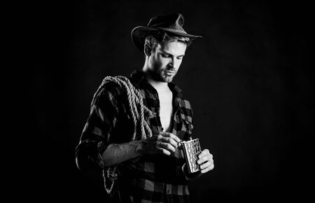 cowboy drink. man checkered shirt on ranch. wild west rodeo. man in hat black background. cowboy with lasso rope. Western. Vintage style man. Wild West retro cowboy. western cowboy portrait Stockfoto
