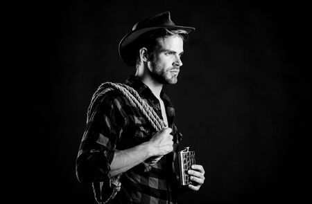 tipsy rider. cowboy with lasso rope. Western. western cowboy portrait. man checkered shirt on ranch. wild west rodeo. man in hat black background. Vintage style man. Wild West retro cowboy