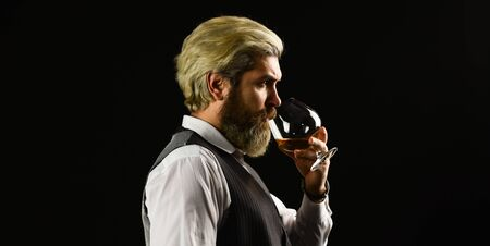 Confident sommelier. Male skilled sommelier estimates alcoholic drink. red wine in wineglasses. bearded man explore taste of wine in restaurant. Checking color and sediments of wine. Wine tasting
