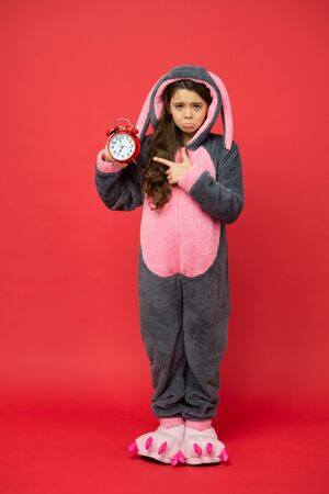 unhappy kid in kigurumi pajama hold alarm clock. time to wake up. sweet dreams. good morning to you. people and bedtime concept. little girl wear easter bunny costume. Early rise. time management