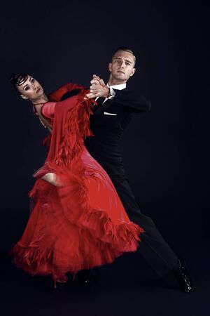 ballrom dance couple in a dance pose isolated on black bachground