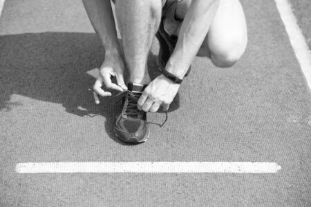 Shoes elite runners wearing marathon. Hands tying shoelaces on sneaker, running surface background. Hands of sportsman with pedometer tying shoelaces on sporty sneaker. Marathon equipment concept.