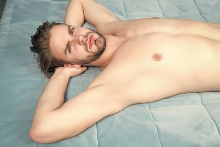 Man with bare torso, chest lie on blue bed cover Stockfoto