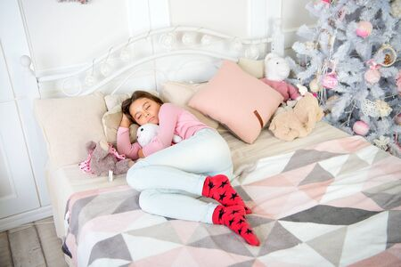 small girl sleeping at home. christmas family holiday. waiting for santa. Winter. morning before Xmas. Sleep. happy new year. Christmas shopping. little child girl with xmas gift. New Year is coming Stock Photo