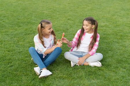 With candy you can put smile on friends face. Happy friends eat lollipops on green grass. Small friends enjoy summer holidays. Free time and leisure. Real friends. True friendship