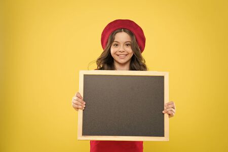 little girl kid with backboard, copy space. board for announcement advertisement. back to school. school shopping sales. kid fashion. happy school girl in parisian beret. We can Serve you better Standard-Bild