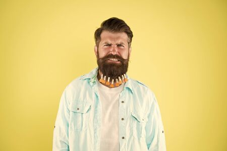 it hurts so much. individual hairstyle for male. man clothespin on beard. brutal hipster with clothespin hearts. bearded man casual style yellow background. valentines day. hair drying in hairdresser