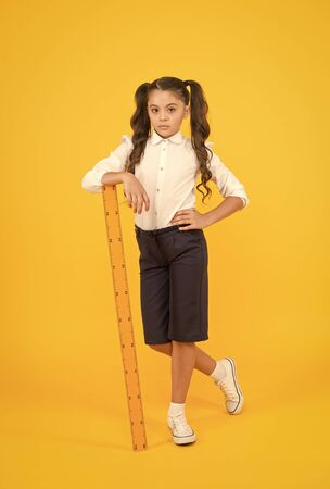 Exploring stem. Education and school concept. Sizing and measuring. Pupil cute girl with big ruler. Geometry school subject. School adorable student study geometry. Kid school uniform hold ruler