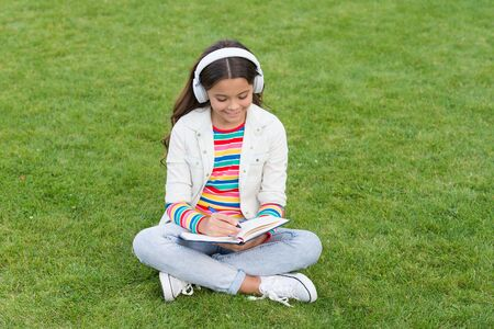 Online learning. Educational podcast. Make It Happen. Listen music outdoors. Kid girl enjoy music sit meadow. Pleasant time. Child headphones listen music. Cool girl headphones listening music Banco de Imagens
