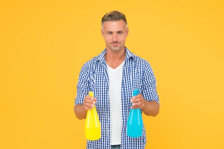 Cleaning made simple. Cleaning man yellow background. Handsome guy hold spray bottles. Using spray disinfectant. Disinfecting home. Domestic cleaning. Cleaning service. Housekeeping and household