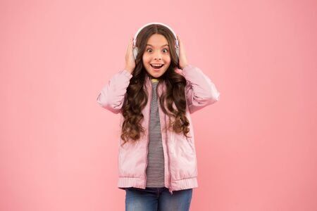 it sounds great. Sound vibrations. Music and technology. Audio sound. Fun and entertainment. Music on. Happy child enjoy listening to sound track. Little girl wear earphones pink background Stock Photo