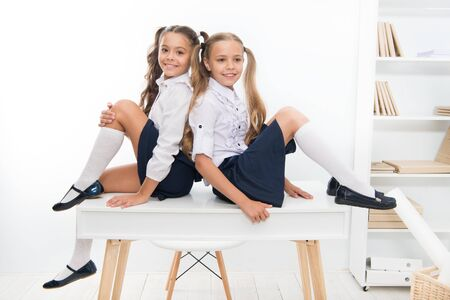 Schoolgirls friends sit on desk. Best friends relaxing. Schoolgirls tidy hairstyle relaxing having rest. School uniform. Rebellious spirit. School club. Little schoolgirls classmates friendly kids