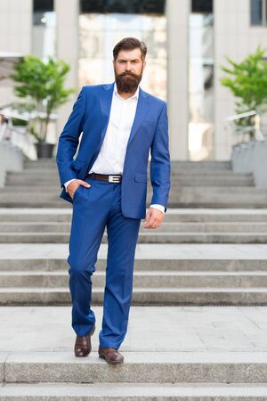 Toward business achievements. Conquer business world. Office worker confidently step on stairs. Bearded man going to work. Business man in modern city. Beginning of working day. Motivated for success