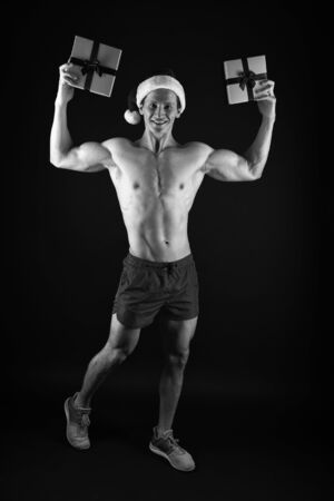 Santa claus for adult girls. Sexy athletic macho muscular chest in santa claus hat. Athlete man wear santa hat. I have gift for you. Handsome santa concept. Macho muscular torso posing with gift box