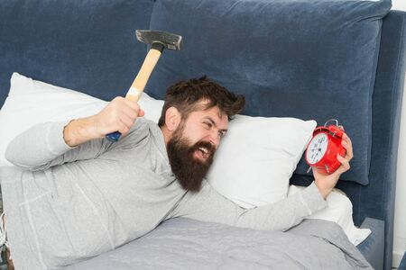 Although you are asleep you may wake up feeling like did not sleep at all. Stages of sleep. Catch up on missed sleep during weekend. Morning awakening. Man awake unhappy with alarm clock ringing Stock Photo