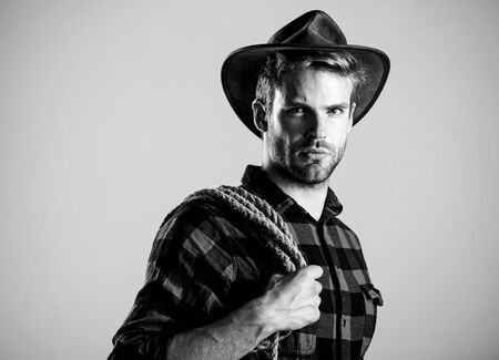 ride any horse. Vintage style man. Wild West retro cowboy. man checkered shirt on ranch. wild west rodeo. man in hat. cowboy with lasso rope. Western. western cowboy portrait