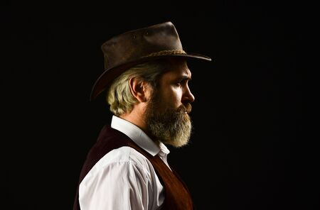 mature cowboy. detective acknowledgement or greeting. trilby hat. man in vintage style wide brimmed hat. Man with retro Hat. brutal bearded hipster in suit vest. mafia gentlemen club Banque d'images