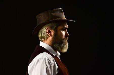 mature cowboy. detective acknowledgement or greeting. trilby hat. man in vintage style wide brimmed hat. Man with retro Hat. brutal bearded hipster in suit vest. mafia gentlemen club Reklamní fotografie