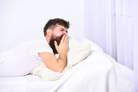 Man in shirt yawning while laying on bed, white wall and curtain on background. Sleepyhead concept. Guy on sleepy tired face yawning. Macho with beard and mustache yawning, relaxing, having nap, rest.